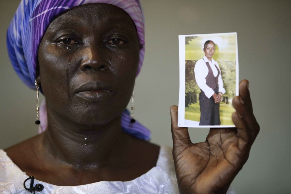 "FILE - In this Monday, May 19, 2014 file photo, Martha Mark, the mother of kidnapped school girl Monica Mark cries as she displays her photo, in the family house, in Chibok, Nigeria. In a new video released late Friday night Oct. 31, 2014, the leader of Nigeria's Islamic extremist group Boko Haram, Abubakar Shekau dashed hopes for a prisoner exchange to get the girls released. ""The issue of the girls is long forgotten because I have long ago married them off,"" he said, laughing. (AP Photo/Sunday Alamba, File)"