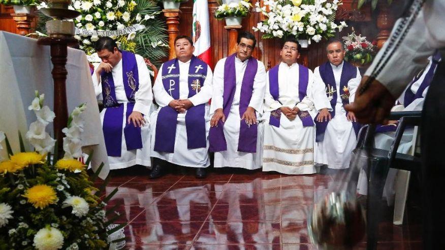 Priesters wonen de begrafenis van de vermoorde Eerwaarde Jose Alfredo Suarez de la Cruz bij.